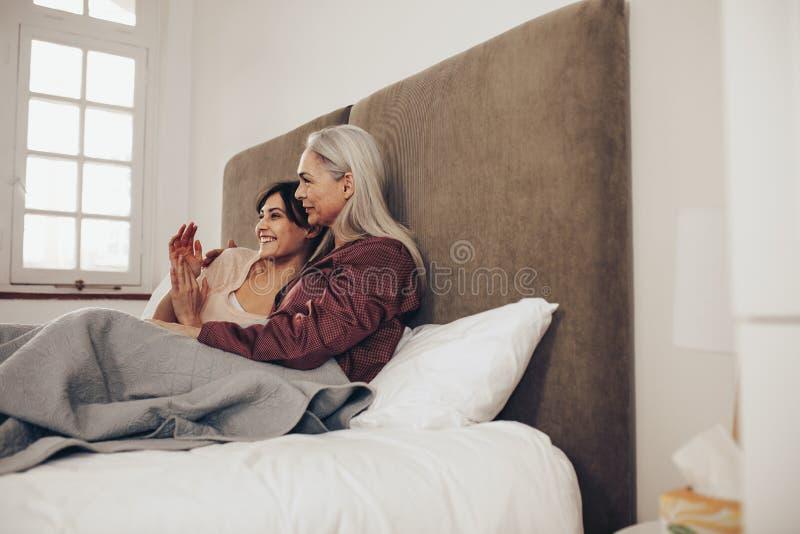 Zijaanzicht van gelukkige moeder en dochterzitting op bed samen Het glimlachen vrouwenzitting naast haar bejaarde moeder en het s stock afbeelding