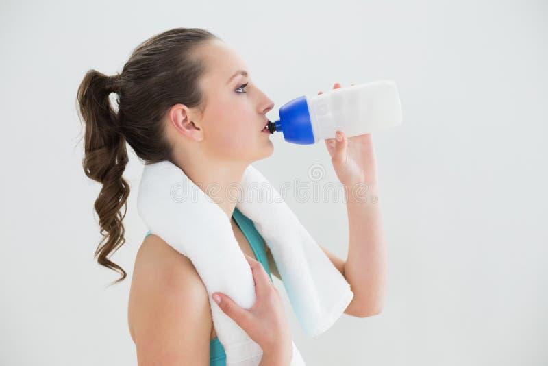 Zijaanzicht van geschikt vrouwen drinkwater bij de gymnastiek stock foto