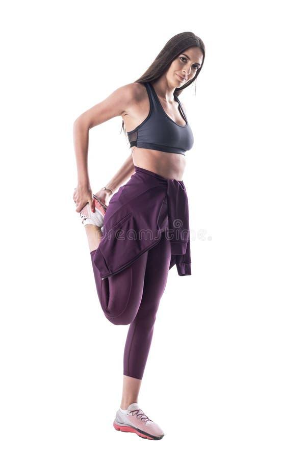 Zijaanzicht van geschikte jonge aantrekkelijke vrouw in mouwloos onderhemd het uitrekken zich been stock foto