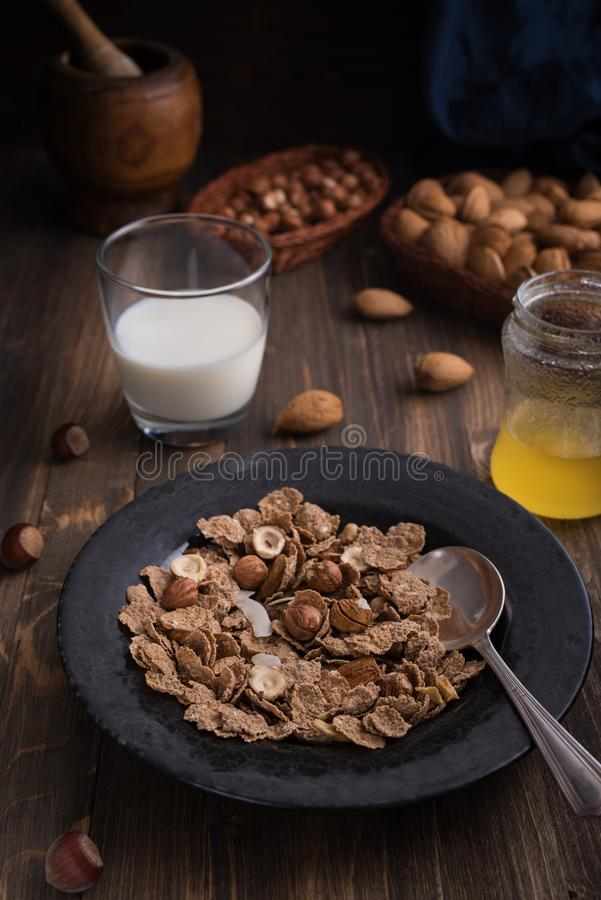 Zijaanzicht van gezond ontbijt met noten en cornflakes op bruine rustieke achtergrond royalty-vrije stock afbeelding
