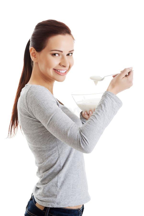 Zijaanzicht van gezonde vrouw die natuurlijke yoghurt eten royalty-vrije stock foto