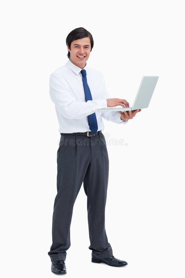 Zijaanzicht van glimlachende kleinhandelaar met zijn laptop stock foto
