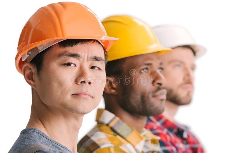 zijaanzicht van groep multi-etnische bouwvakkers stock fotografie