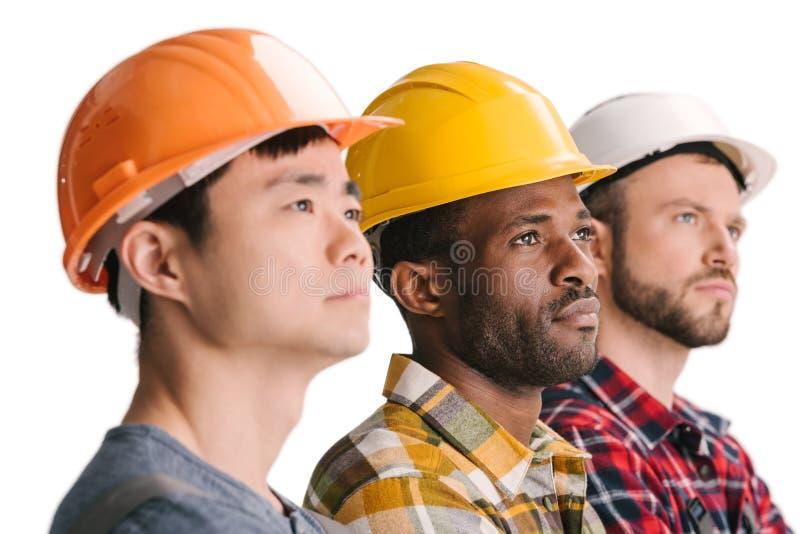 zijaanzicht van groep multi-etnische nadenkende bouwvakkers stock afbeeldingen