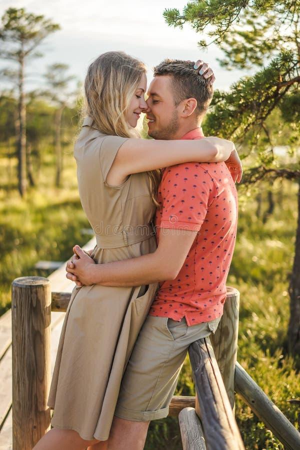 zijaanzicht van hartelijk paar die op houten brug met groene installaties koesteren royalty-vrije stock afbeeldingen