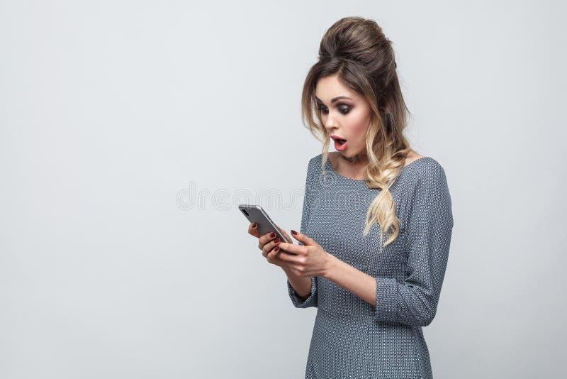 Zijaanzicht van het geschokte mooie bloggertiener dragen in grijze kleding met vlecht bij hoofd status, het gebruiken van smartph stock fotografie