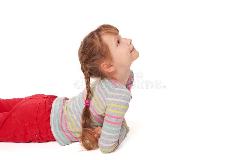 Zijaanzicht van het glimlachen kindmeisje het liggen op de vloer royalty-vrije stock afbeelding