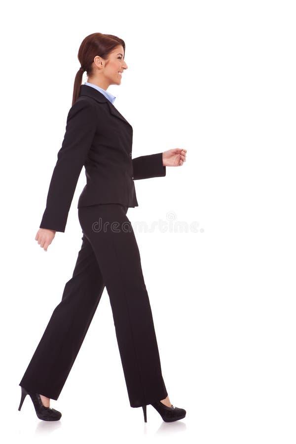 Zijaanzicht van het jonge bedrijfsvrouw lopen stock afbeelding