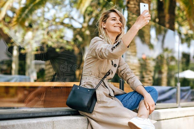 Zijaanzicht van het mooie jonge vrouw glimlachen terwijl het houden van smartphone en het maken van zelfportret tegen palmen royalty-vrije stock foto