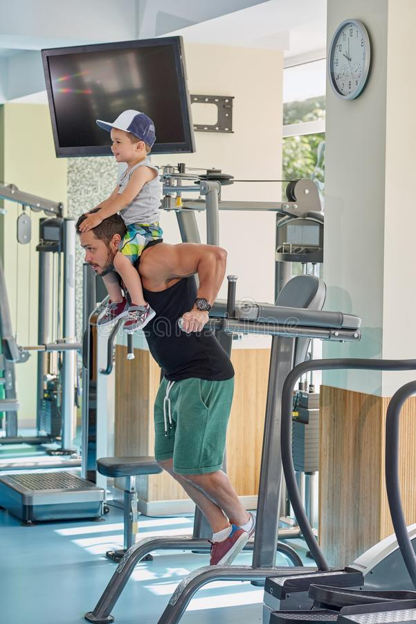 Zijaanzicht van het spiervader uitoefenen in gymnastiek die zijn kleine zoon op hals houden stock fotografie
