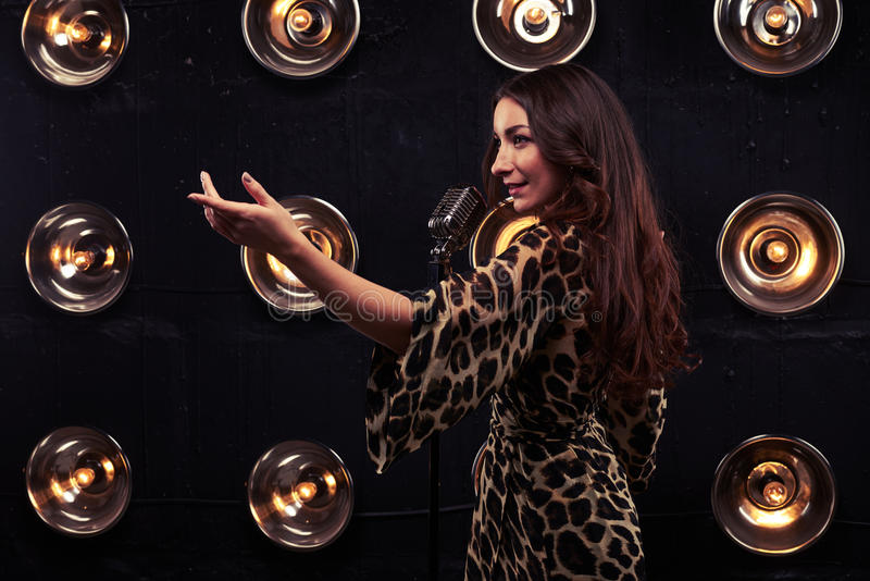 Zijaanzicht van het verleiden van vrouw het wenken met hand het zingen in mic stock afbeelding