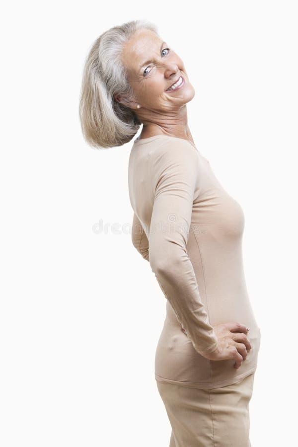 Zijaanzicht van hogere vrouw in toevallig met handen op heupen tegen witte achtergrond royalty-vrije stock foto's