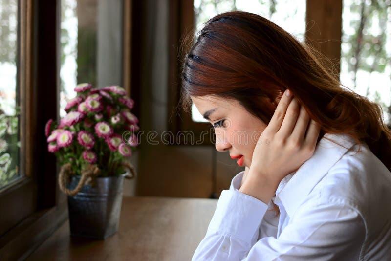 Zijaanzicht van jonge aantrekkelijke Aziatische bedrijfsvrouwenzitting in koffiekoffie royalty-vrije stock fotografie
