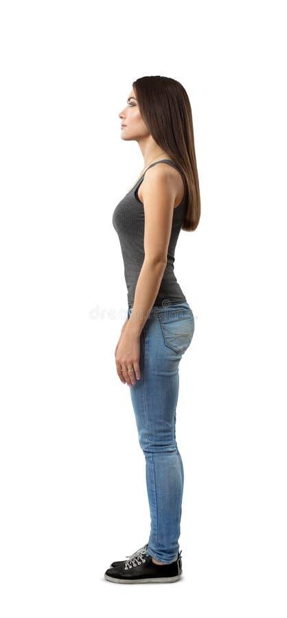 Zijaanzicht van jonge aantrekkelijke vrouw in grijze sleeveless bovenkant en jeans die zich met die wapens aan kanten bevinden op stock foto's