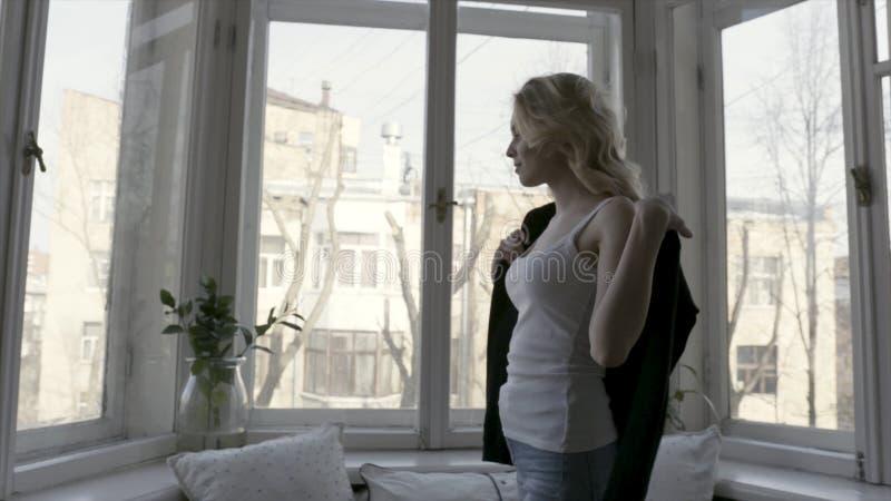 Zijaanzicht van jonge en mooie blonde vrouw in jeans en wit mouwloos onderhemd die zwarte cardigan van start gaan actie Meisje royalty-vrije stock foto