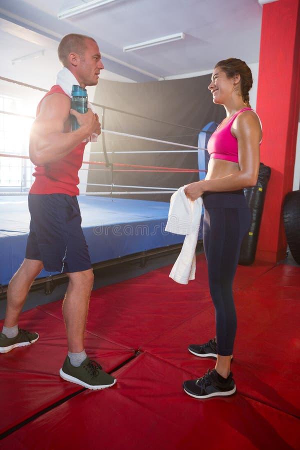 Zijaanzicht van jonge mannelijke en vrouwelijke atleten die door boksring spreken stock afbeelding