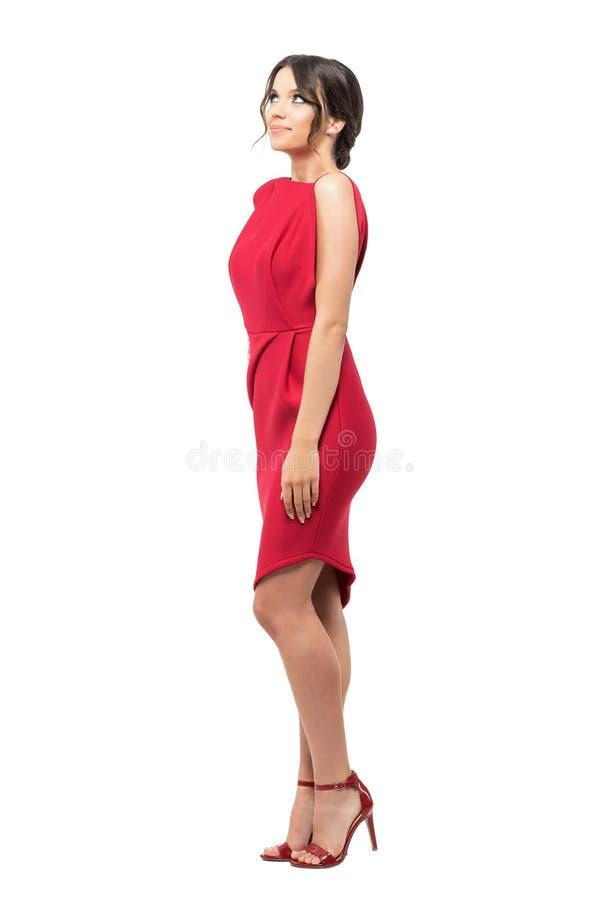 Zijaanzicht van jonge mooie vrouw die in rode avond korte kleding omhoog glimlachend kijken royalty-vrije stock foto's