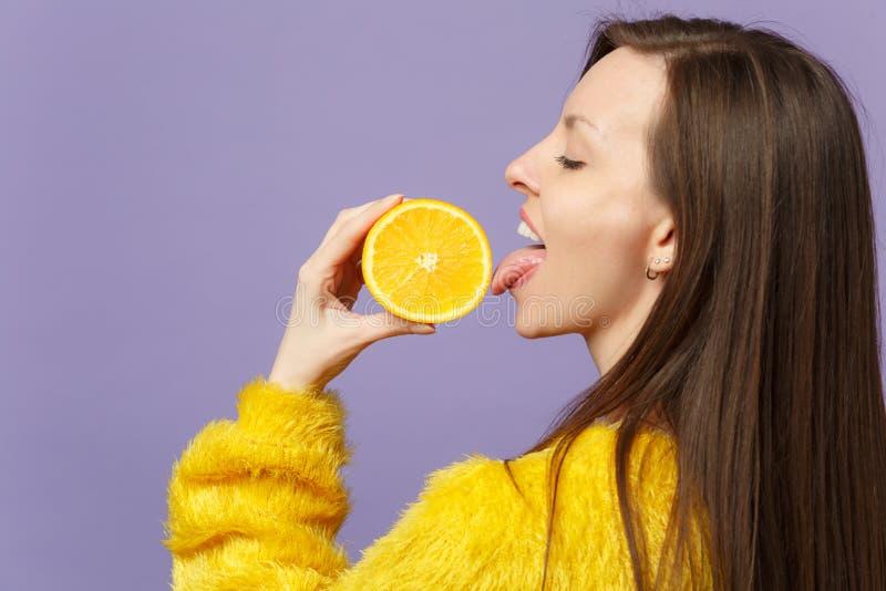 Zijaanzicht van jonge vrouw in de greep die van de bontsweater helft van vers rijp oranje fruit likken die op violette pastelkleu stock fotografie