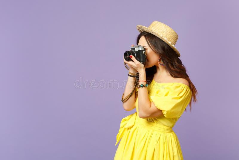 Zijaanzicht van jonge vrouw in gele kleding, de zomerhoed die beelden op retro uitstekende die fotocamera nemen op pastelkleur wo royalty-vrije stock foto