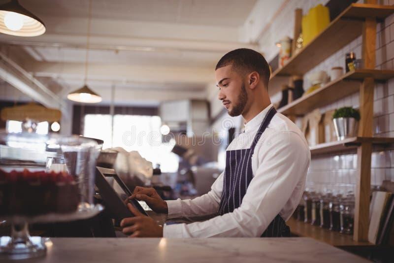 Zijaanzicht van knappe jonge kelner die computer met behulp van bij teller royalty-vrije stock fotografie