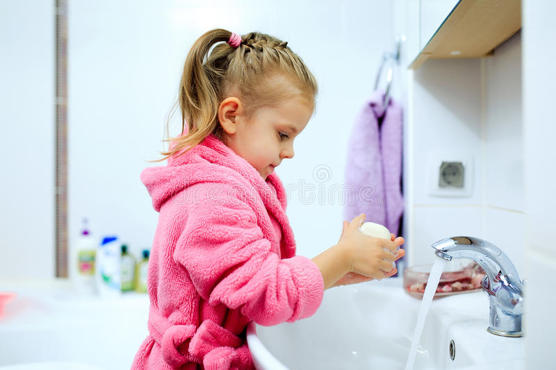 Zijaanzicht van leuk meisje met paardestaart in roze badjas die haar handen wassen royalty-vrije stock fotografie