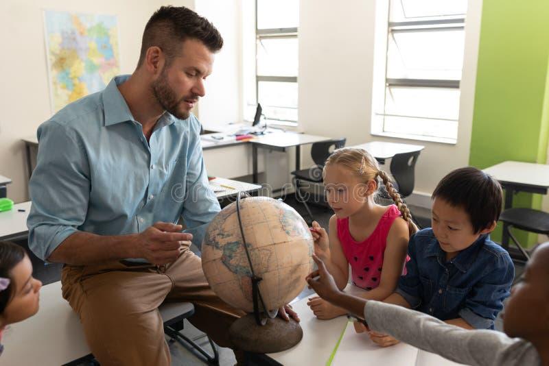 Zijaanzicht van mannelijke leraar die zijn jonge geitjes over aardrijkskunde onderwijst door bol in klaslokaal te gebruiken stock foto