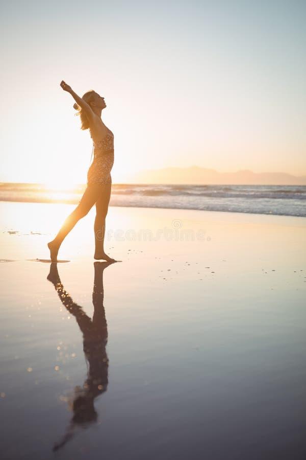Zijaanzicht van onbezorgde vrouw met wapens uitgestrekt bij strand royalty-vrije stock fotografie