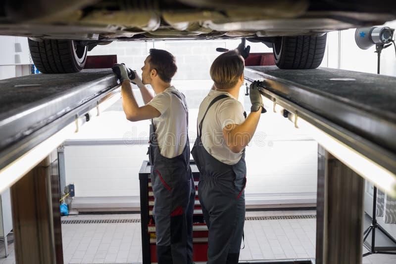 Zijaanzicht van onderhoudsingenieurs die auto in reparatiewerkplaats onderzoeken stock foto