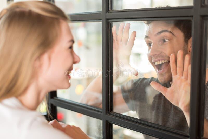 zijaanzicht van paar in liefde die elkaar door glasdeur bekijken stock foto