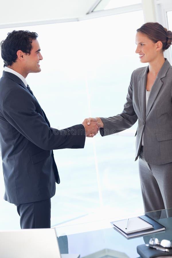 Zijaanzicht van partner het akkoord gaan met een overeenkomst stock foto