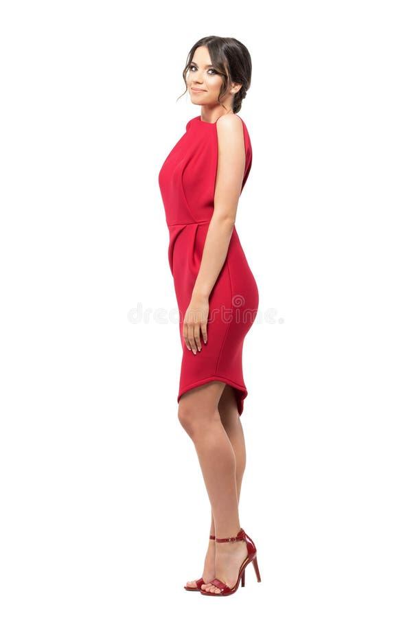 Zijaanzicht van schitterende glimlachende vrouw die in rode avondtoga camera bekijken stock foto's