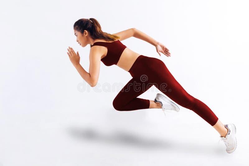 Zijaanzicht van slank Aziatisch wijfje die in rode sportkleding snel tegen witte achtergrond sprinten royalty-vrije stock fotografie