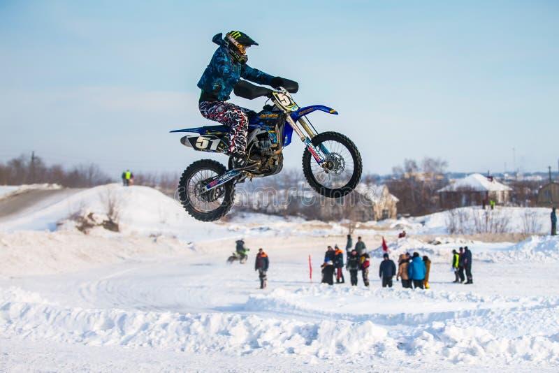 Zijaanzicht van sprong en vlucht van motorracer over sneeuwspoor stock afbeelding