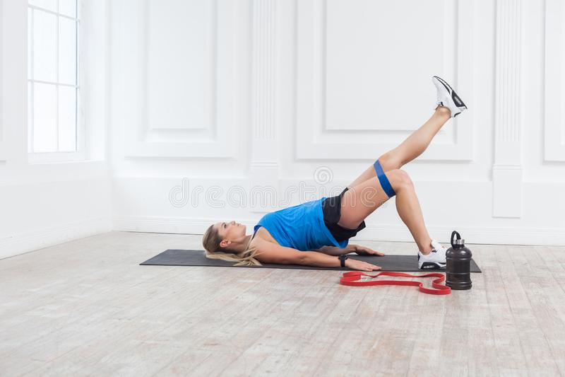 Zijaanzicht van sterke en geschikte atletische jonge Kaukasische vrouw in sportwear met banden die benen opleiden en glutes spier royalty-vrije stock foto's