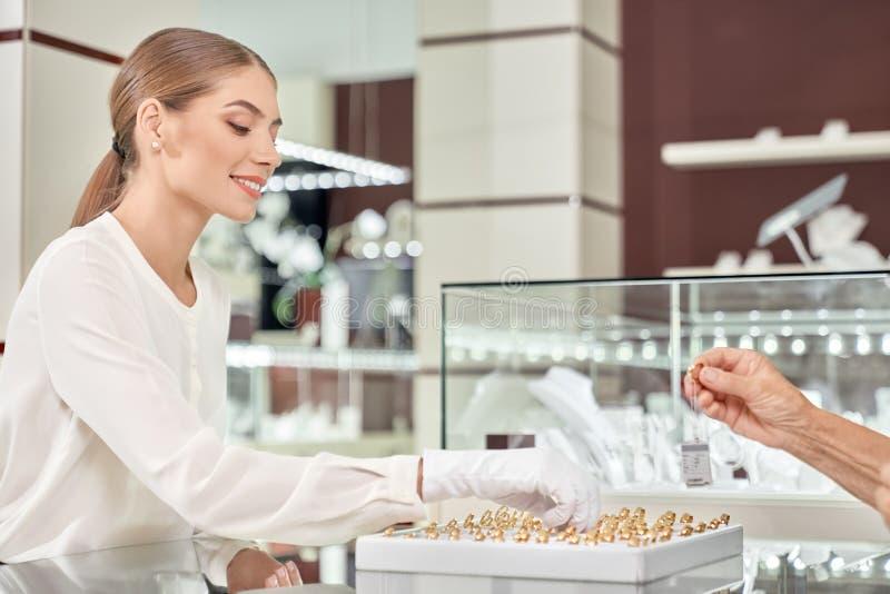 Zijaanzicht van verkoper die gouden producten adviseren aan klant stock foto