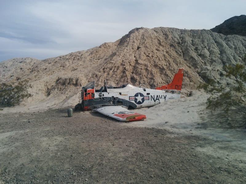 Zijaanzicht van verpletterd Marinevliegtuig op kleine woestijnheuvel stock foto