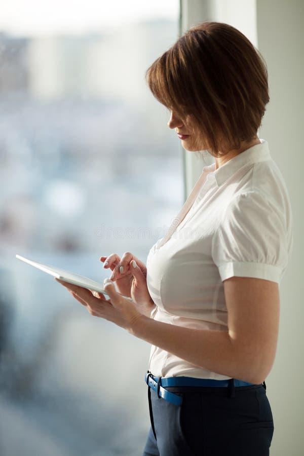 Zijaanzicht van volwassen vrouw die tablet gebruiken stock foto