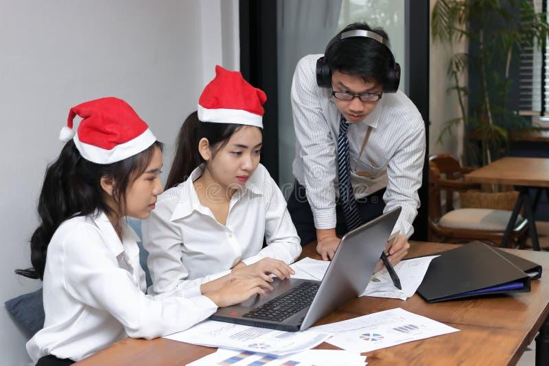 Zijaanzicht van vrolijke jonge Aziatische bedrijfsmensen in Kerstmanhoeden die laptop in bureau met behulp van Kerstmis of Kerstm stock foto