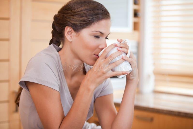 Zijaanzicht van vrouw die van een kop van koffie geniet royalty-vrije stock foto's