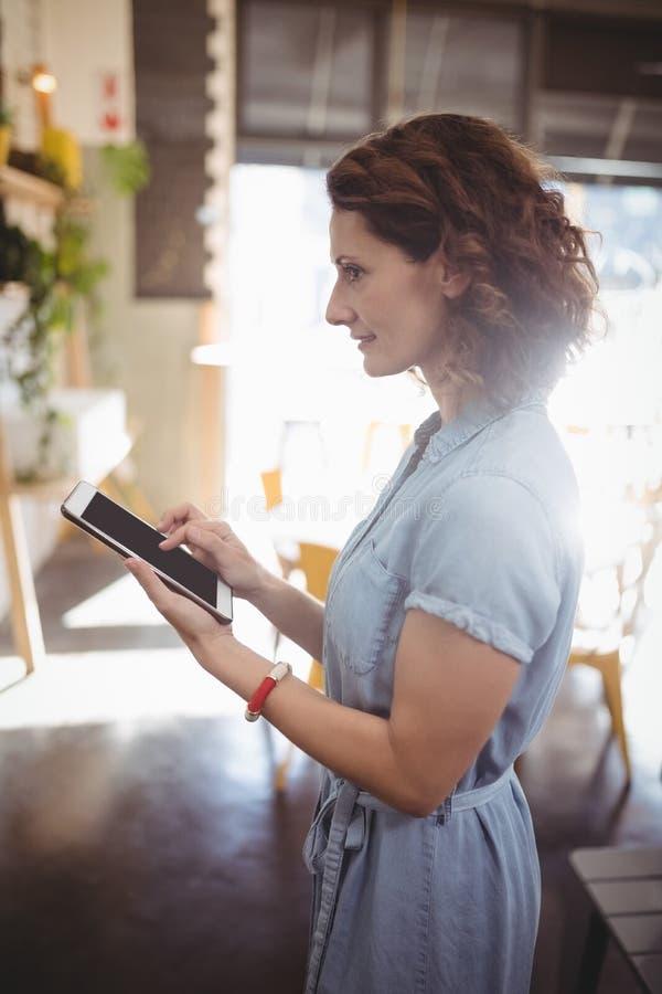 Zijaanzicht van vrouwelijke klant die tablet gebruiken bij koffie royalty-vrije stock foto's