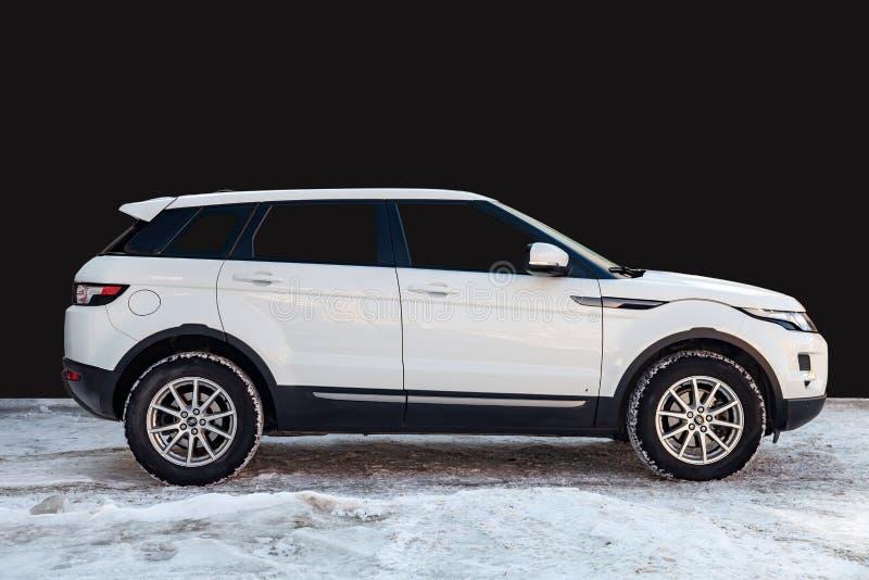 Zijaanzicht van Waaier Rover Land Rover Evoque in witte kleur na het schoonmaken vóór verkoop die zich op sneeuw met zwarte muura royalty-vrije stock afbeeldingen