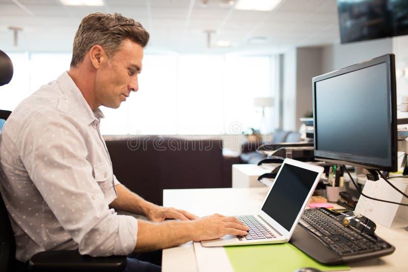 Zijaanzicht van zakenman die laptop in bureau met behulp van royalty-vrije stock foto's