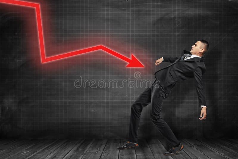Zijaanzicht van zakenman in zwart kostuum die achteruit het proberen leunen om rode grafiekpijl te ontwijken die op hem op zwarte royalty-vrije stock afbeeldingen