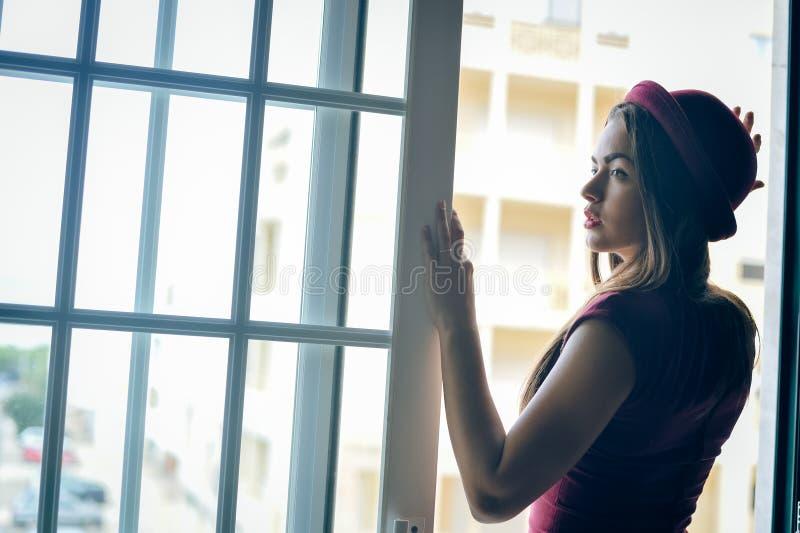 Zijaanzichtfoto van aantrekkelijke modieuze dame in rode hoed die zich in deuropening bevinden die afstand onderzoeken stock fotografie