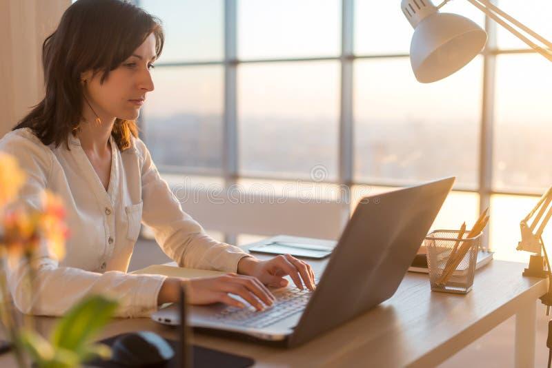 Zijaanzichtfoto van een vrouwelijke programmeur die laptop, het werken die, het typen met behulp van, Internet surfen op het werk stock afbeelding