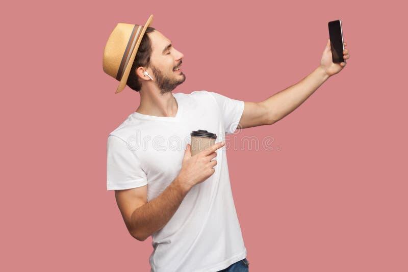 Zijaanzichtportret van de knappe gebaarde jonge hipstermens in wit overhemd en toevallige hoed die en selfie foto met glimlach st stock afbeeldingen