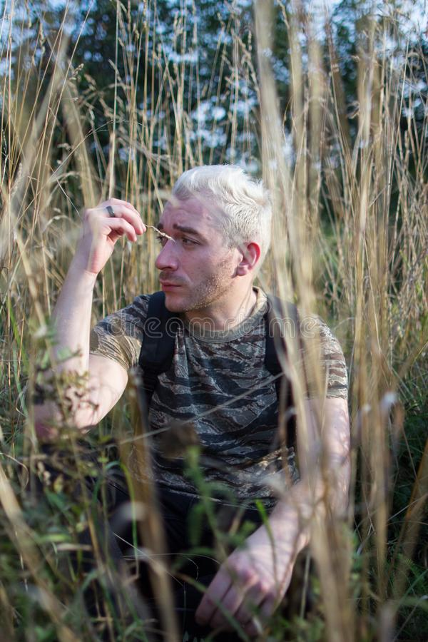 Zijaanzichtportret van een jonge droevige aantrekkelijke gebaarde zitting van de blondekerel op het gebiedsgras royalty-vrije stock foto