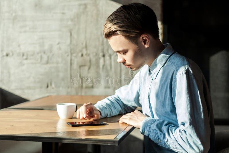 Zijaanzichtportret van ernstige aandachtige jonge zakenman in zitting die van het denim de blauwe overhemd telefoon met behulp va royalty-vrije stock fotografie