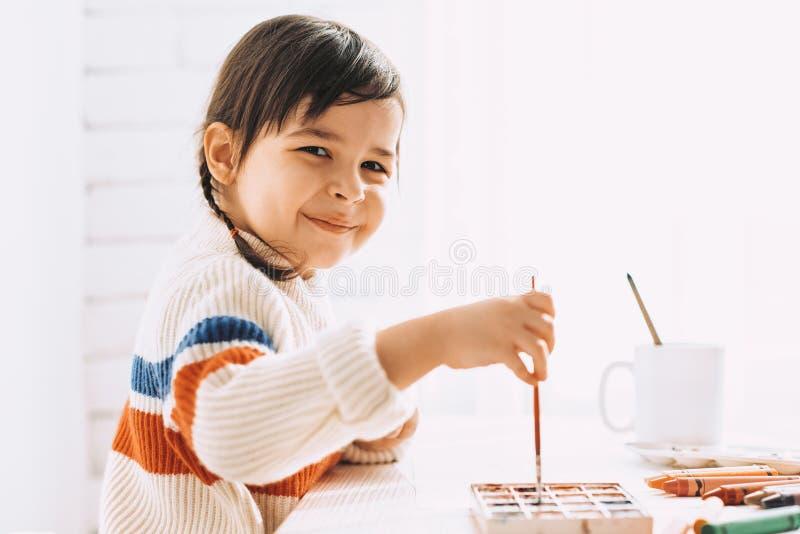 Zijaanzichtportret van het leuke het glimlachen meisje schilderen en thuis het trekken met borstel en waterverf op wit bureau stock foto's