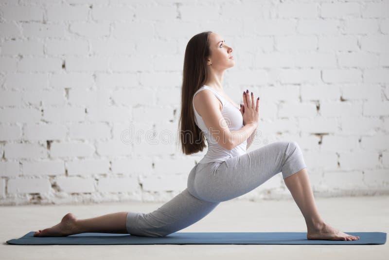 Zijaanzichtportret van jonge vrouw die yoga in witte zolder doen royalty-vrije stock foto's